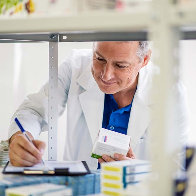 Male pharmacist checking medicines inventory at hospital pharmacy